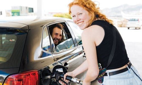 redheaded woman pumping gas