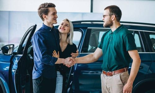 Young couple buying car from dealership