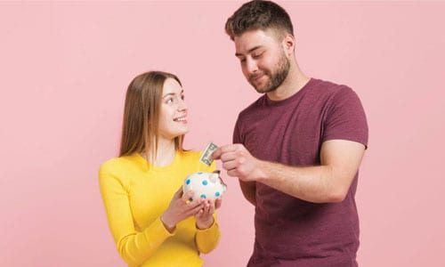 happy couple putting money in piggy bank