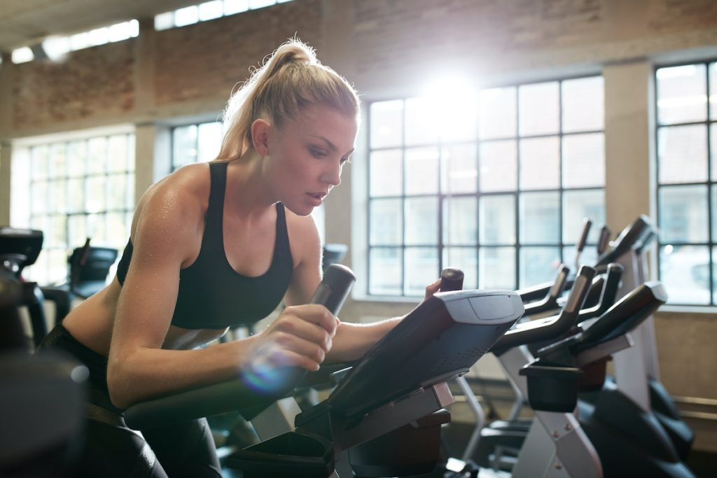 Woman working out on exercise bike at the gym