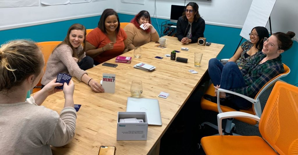 a group of girls at a table playing a game and laughing