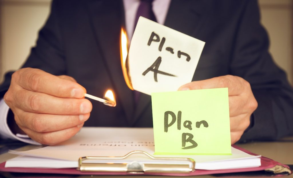 strategic reboot don't redo reboot your plans - Plan B against plan A. A man holds a burning sticker in his hand as a symbol of the fact that the plan has failed and something has gone wrong.